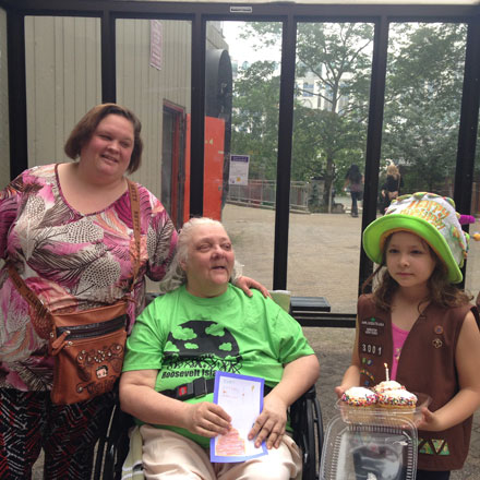 A Volunteer from Roosevelt Island Girl Scouts Troop 3001 Presenting Birthday Cupcakes to a Senior